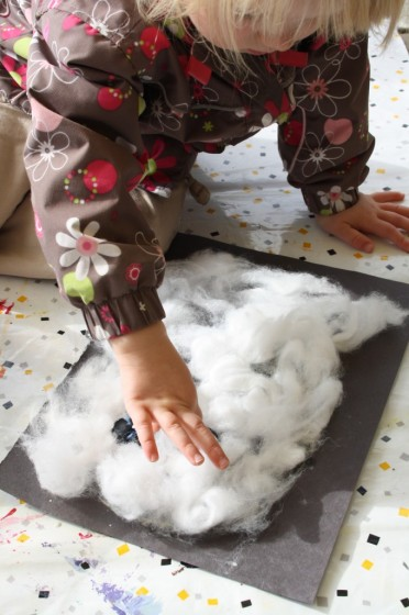 Toddler making a cotton ball ghost craft