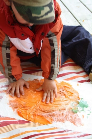 toddler smoosh painting a pumpkin with plastic wrap
