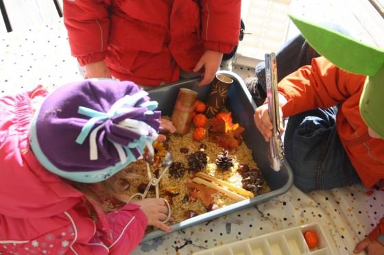 Preschoolers examining November sensory bin