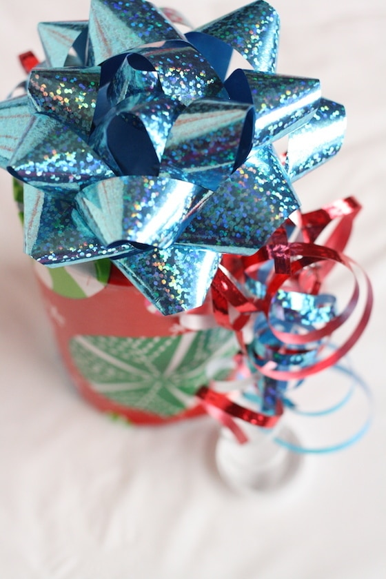 tin can wrapped in wrapping paper with blue bow and ribbon
