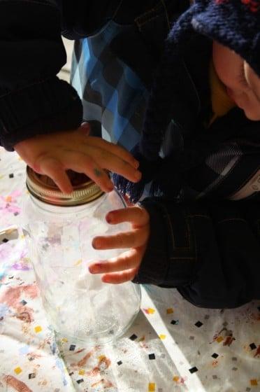 child putting lid on jar