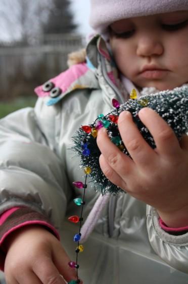 toddler examining christmas tree in sensory bin