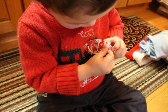 toddler lacing paper candy cane with white yarn