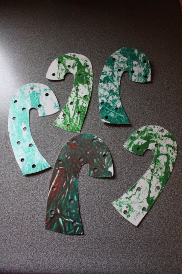 paper candy canes painted green with holes punched in them