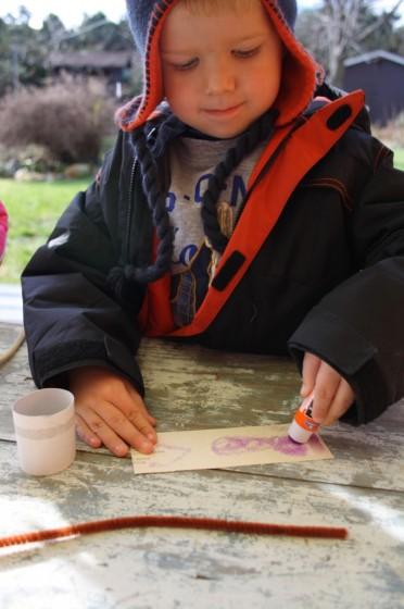 preschooler gluing paper around cardboard roll