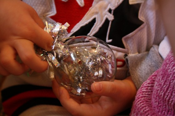 toddler filling clear glass Christmas ornament