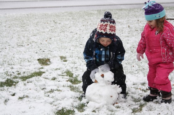 3 year olds building snowman