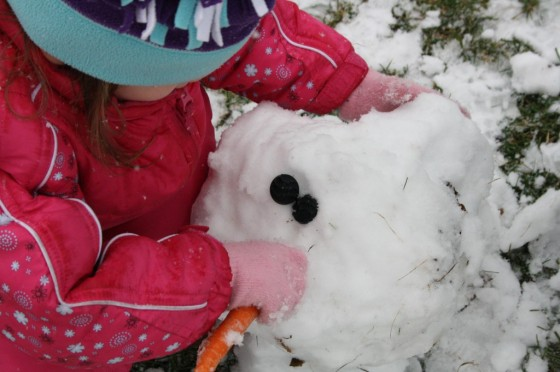 toddler putting carrot nose on snowman