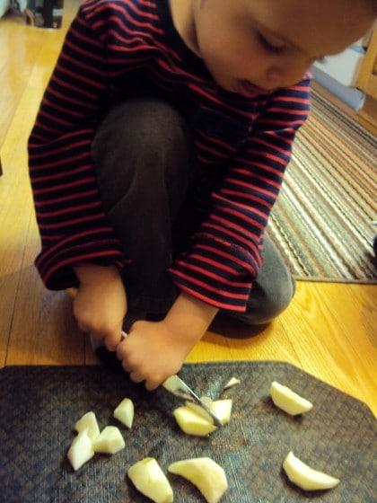 preschooler cutting apples with butter knife
