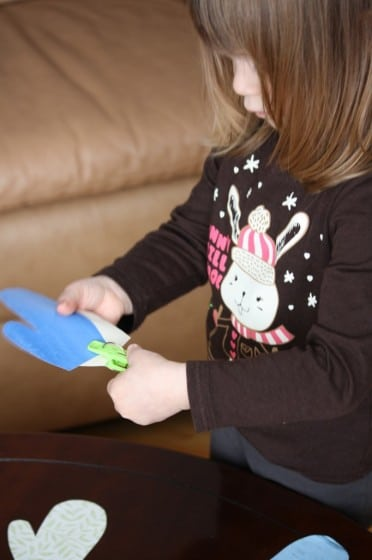 preschooler matching up coloured paper mittens