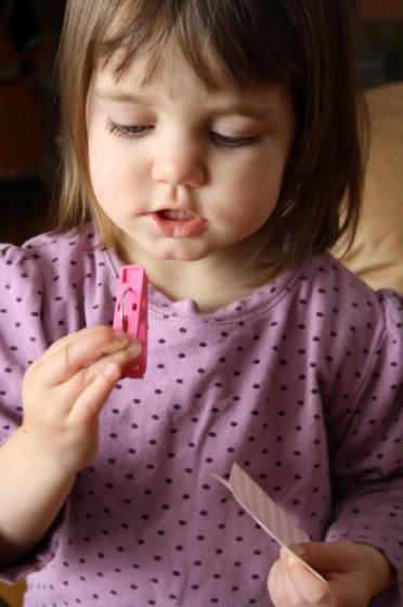 toddler clipping paper mittens together with clothespin