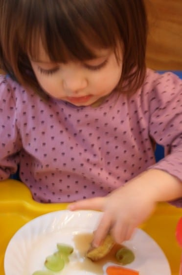 toddler eating french toast in booster