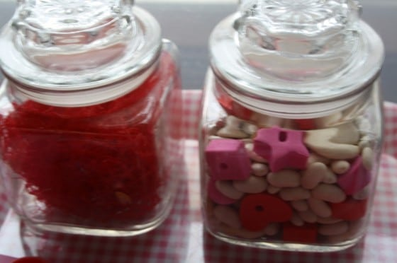 glass jars filled with small red, pink and white items for toddlers to examine