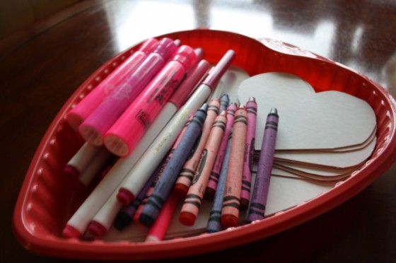 red plastic heart shaped tray with crayons markers and white cardboard hearts