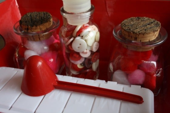 glass jars filled red, white and pink buttons, pom poms and beads, red scoop