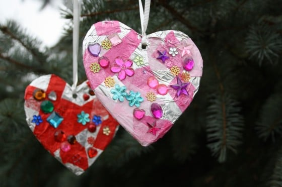 two tin foil hearts decorated with gems hanging in tree