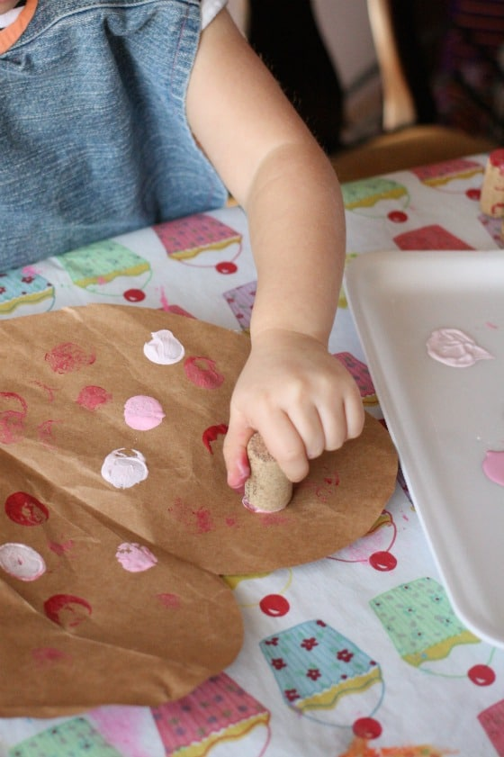 child stamping valentines hearts with corks