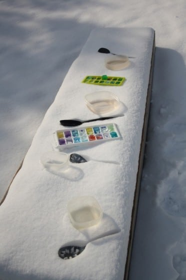 snow-covered bench with coloured ice cubes and plastic spoons