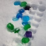 playing with coloured ice cubes in the snow