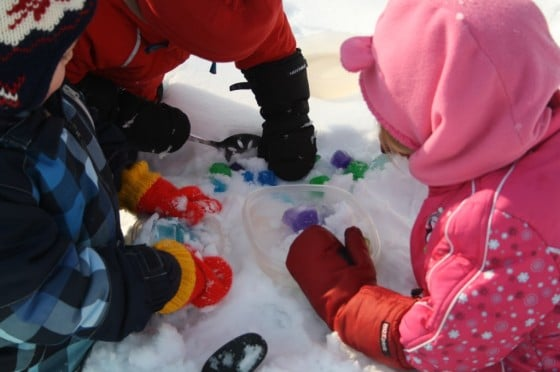 toddlers and preschoolers playing with coloured ice cubes in the snow