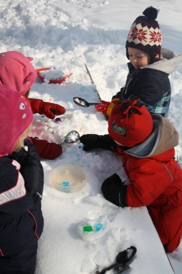 preschoolers playing in snow with coloured ice cubes