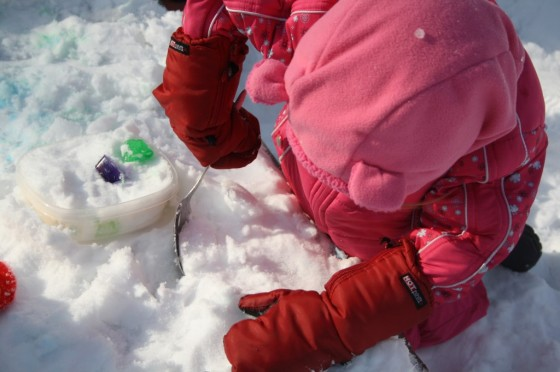 child digging in snow with spoon