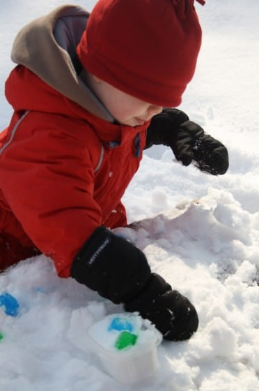 child playing with blue ice cubes in snow