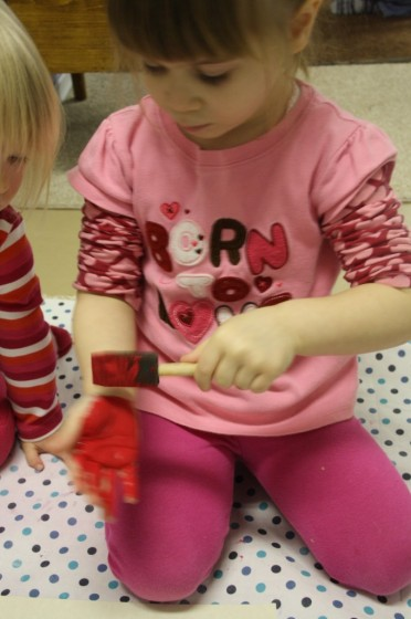 toddlers painting their hands red with sponge paintbrush