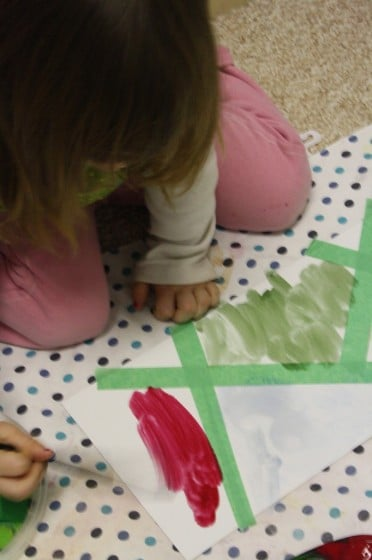 Toddler filling in sections of tape resist with watercolour paints