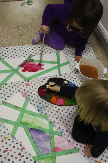 Several children making tape resist art at daycare