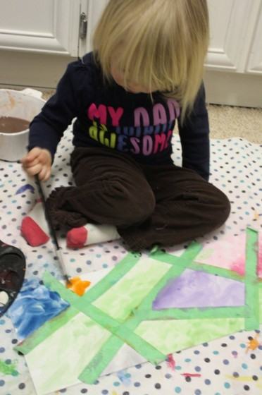 2 year old sitting on the floor, painting