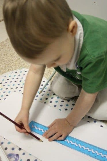 Toddler using pencil and ruler
