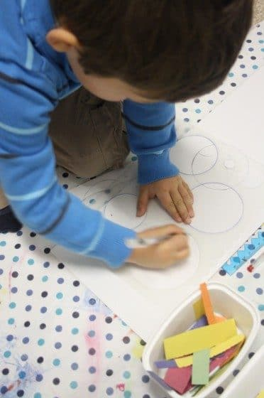 Preschooler drawing circles with stencil