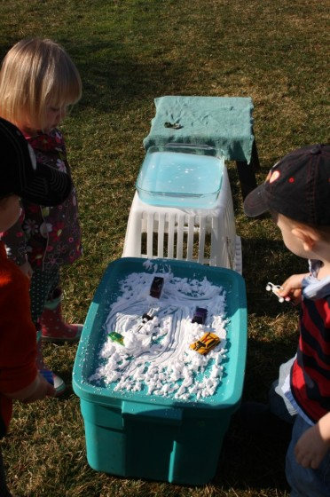 toddlers standing at pretend play car wash stations