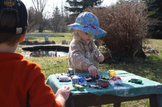 toddler drying car on table with tea towel