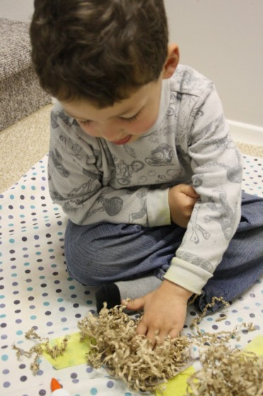 preschooler making paper nest