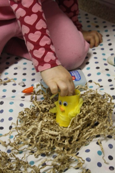 preschooler putting toilet roll chick in paper nest