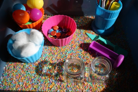 Sensory bin with coloured rice, jars, plastic eggs and glass beads