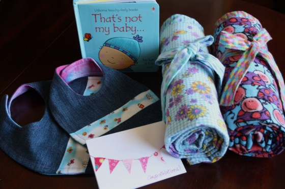homemade baby blankets, bibs, card and a book