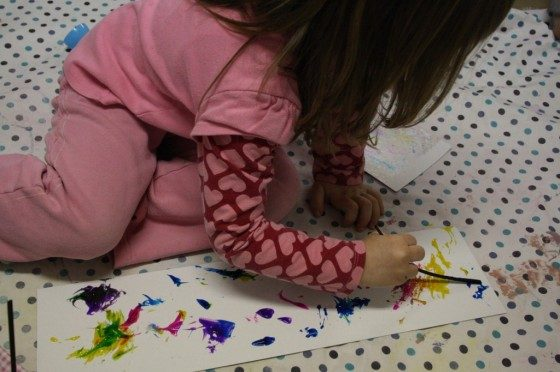 Kids pouring paint to prepare for their marbleized Easter craft.