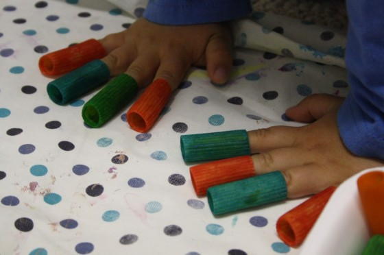 child wearing dyed pasta on fingers