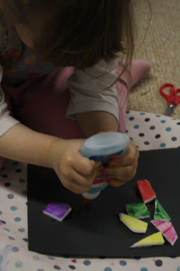 preschooler squeezing glue on black construction paper