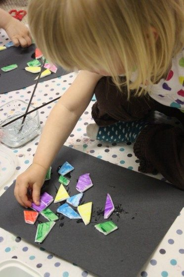 toddler gluing painted styrofoam pieces into mosaic art