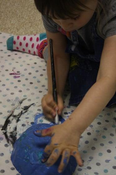 preschooler painting paper mache bowl blue