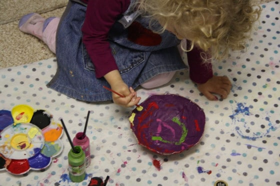 child painting paper mache bowl with acrylic craft paint