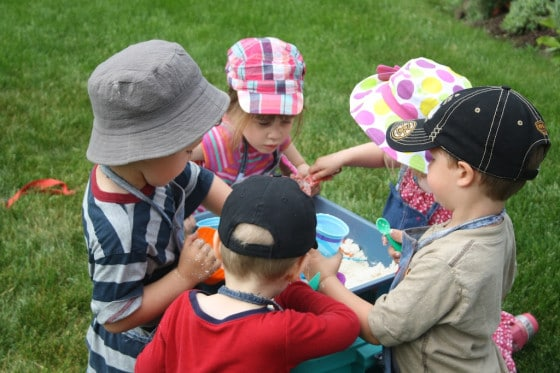 kids gathered round a bin of cloud dough\