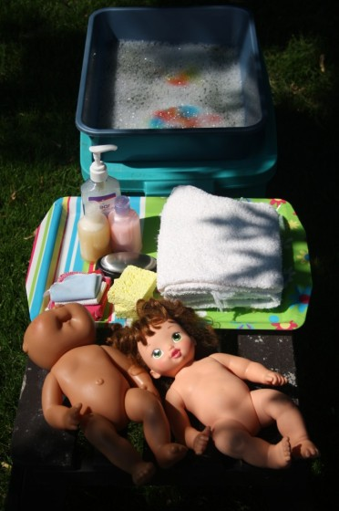 Dolls, soap, shampoo and basin of water for doll bath pretend play