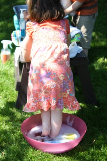toddler standing in bowl of soapy water