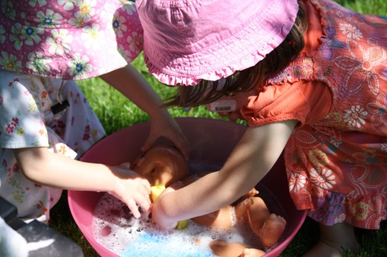 little girls washing dolls in soapy water