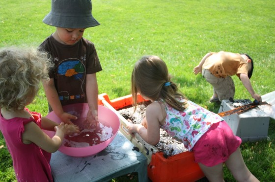 4 preschoolers playing with cars in mud